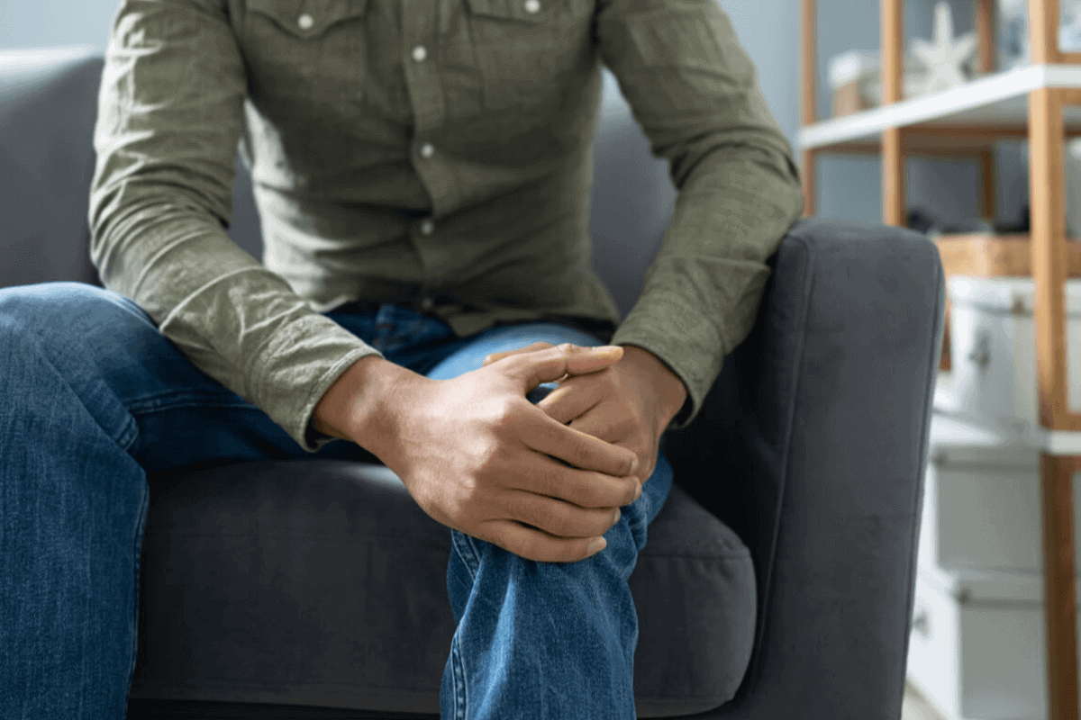 man sitting on couch holding his knee