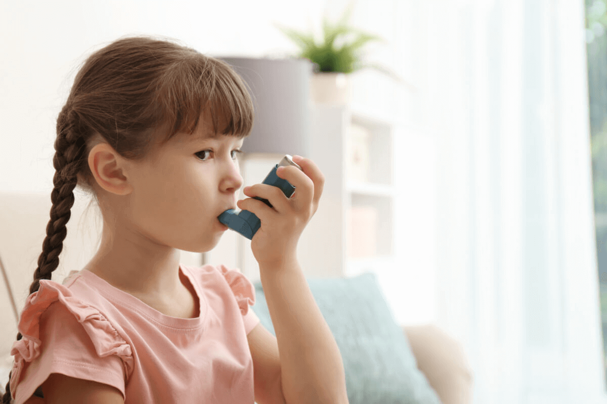 little girl using a puffer for asthma