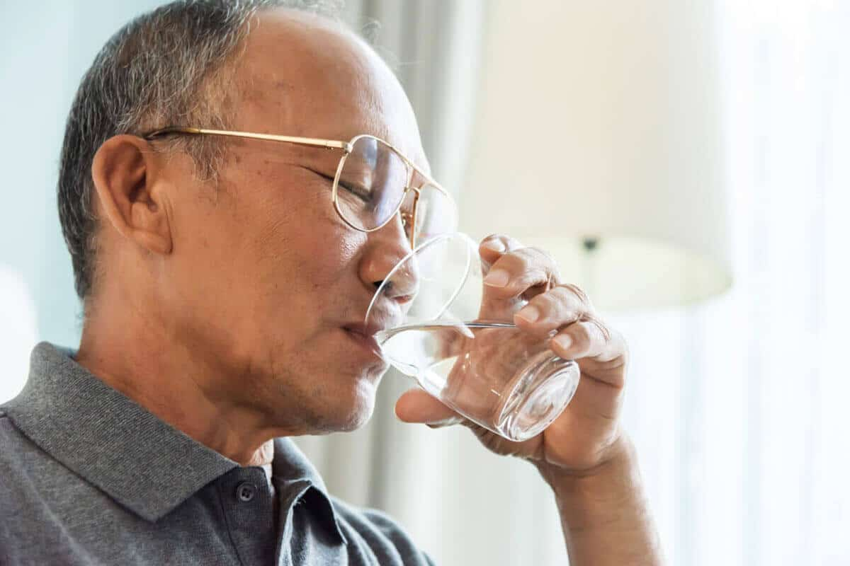 elder man drinking water from a glass