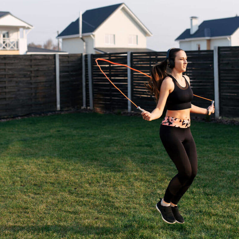 woman skipping rope in her backyard