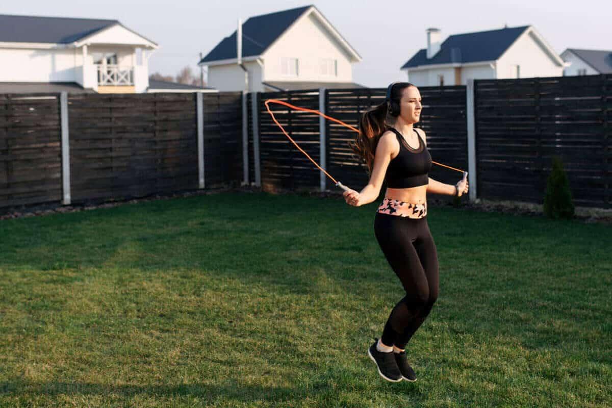 woman skipping rope in her backyard