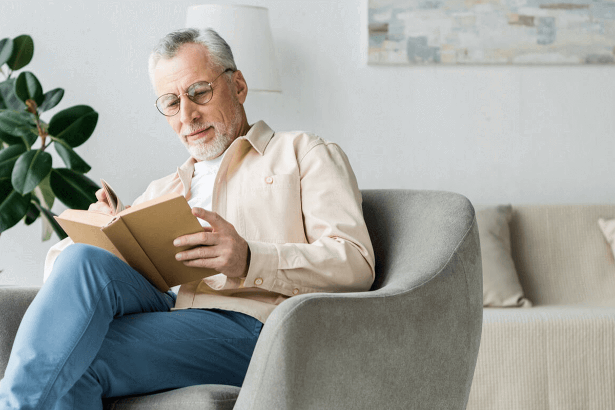 man sitting on couch in his living room reading a book