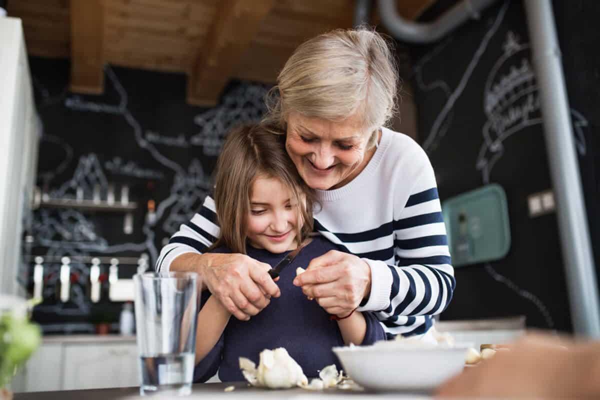 woman helping young girl peel garlic in kitchen