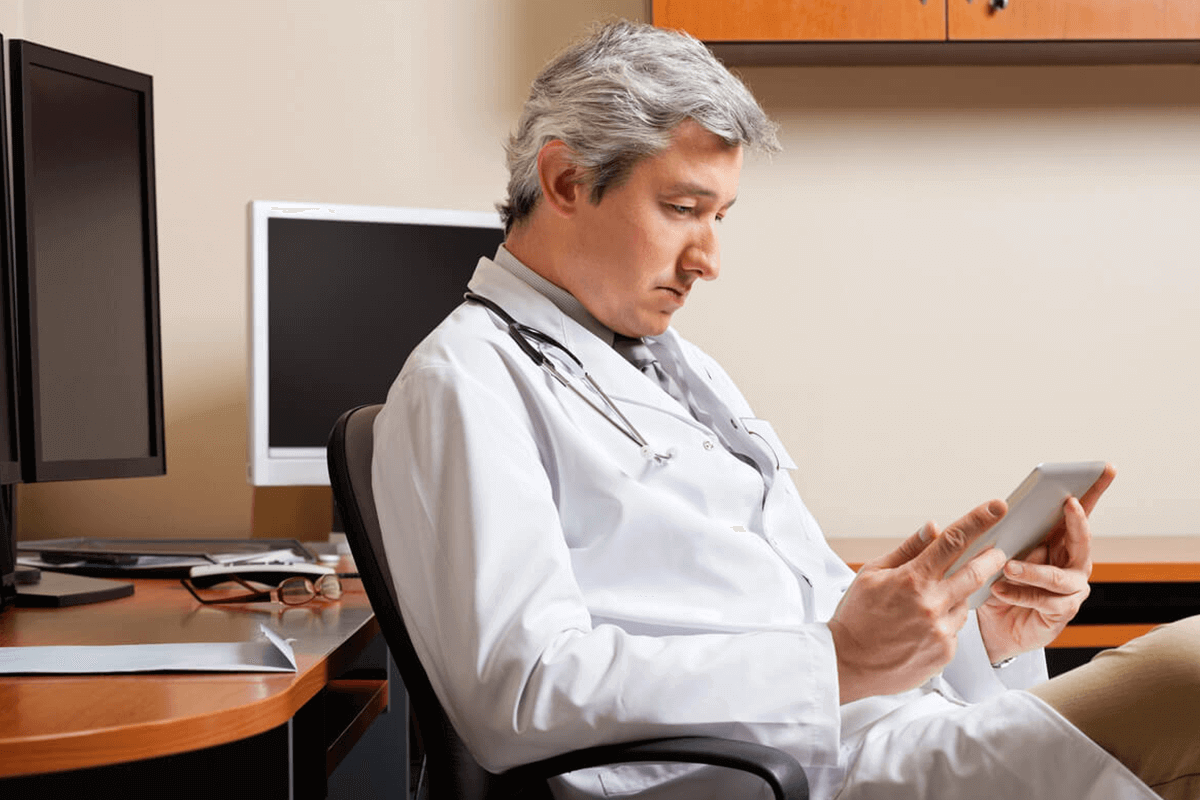 doctor in office at desk looking at iPad/tablet