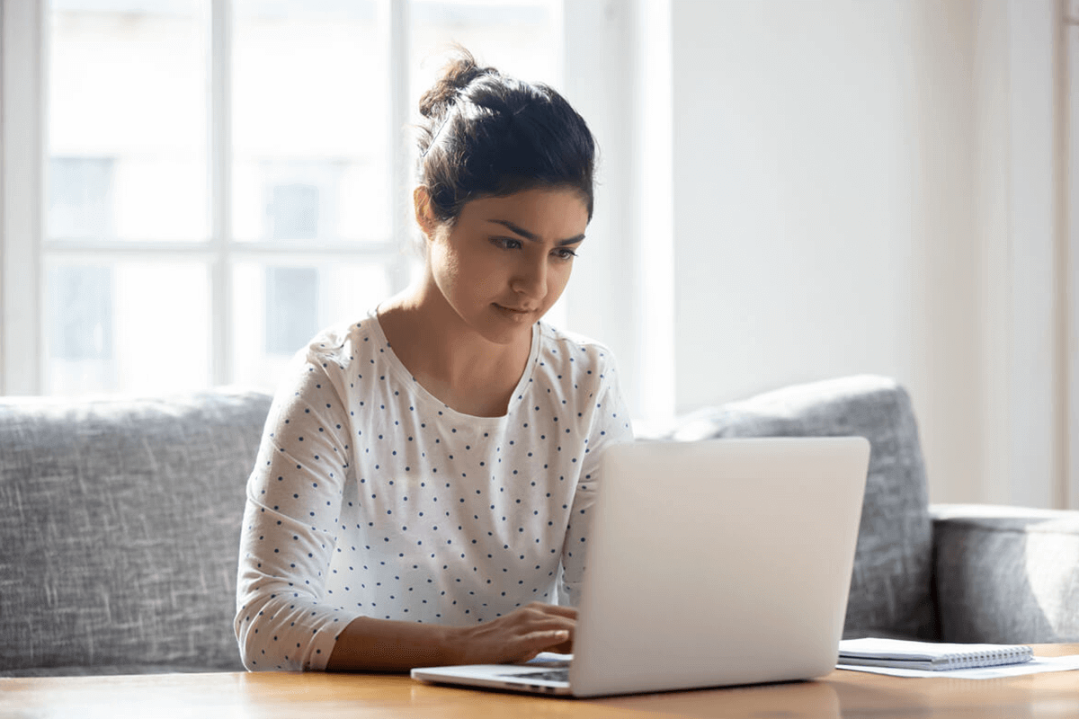 woman sitting on her couch working on her laptop