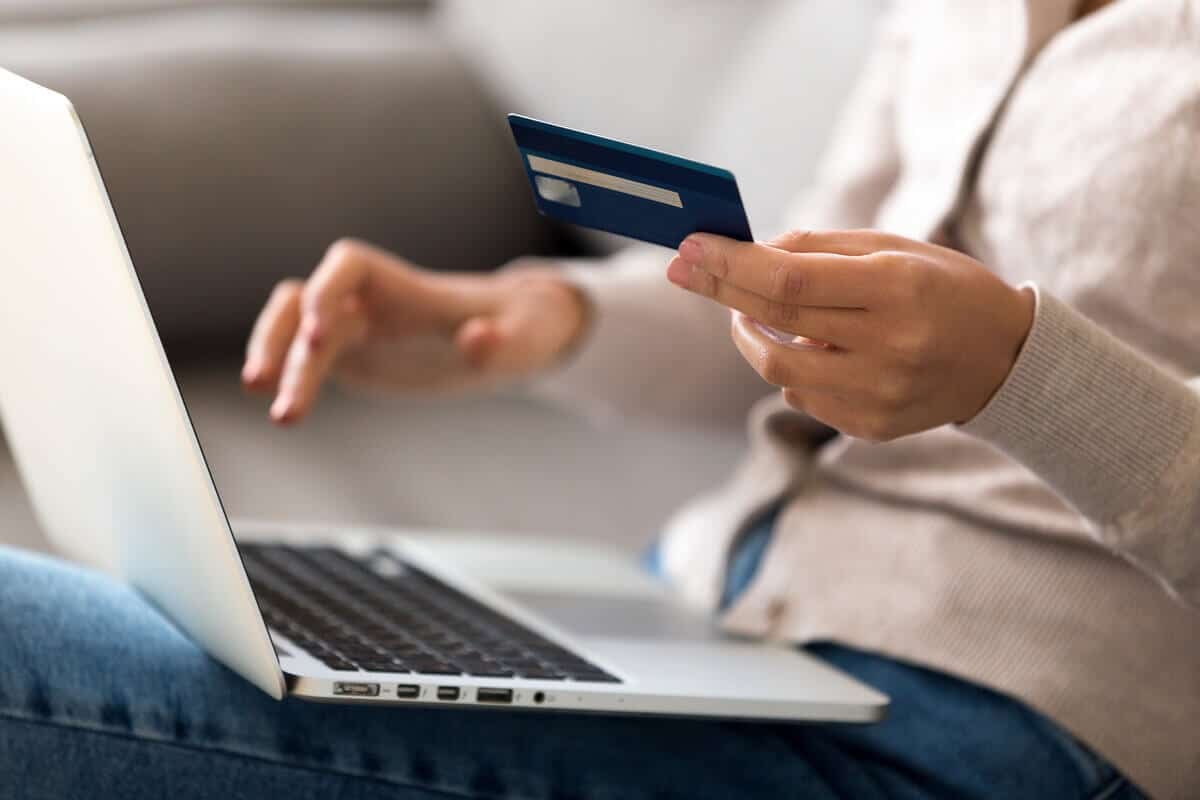 close up of person holding card and paying online on laptop