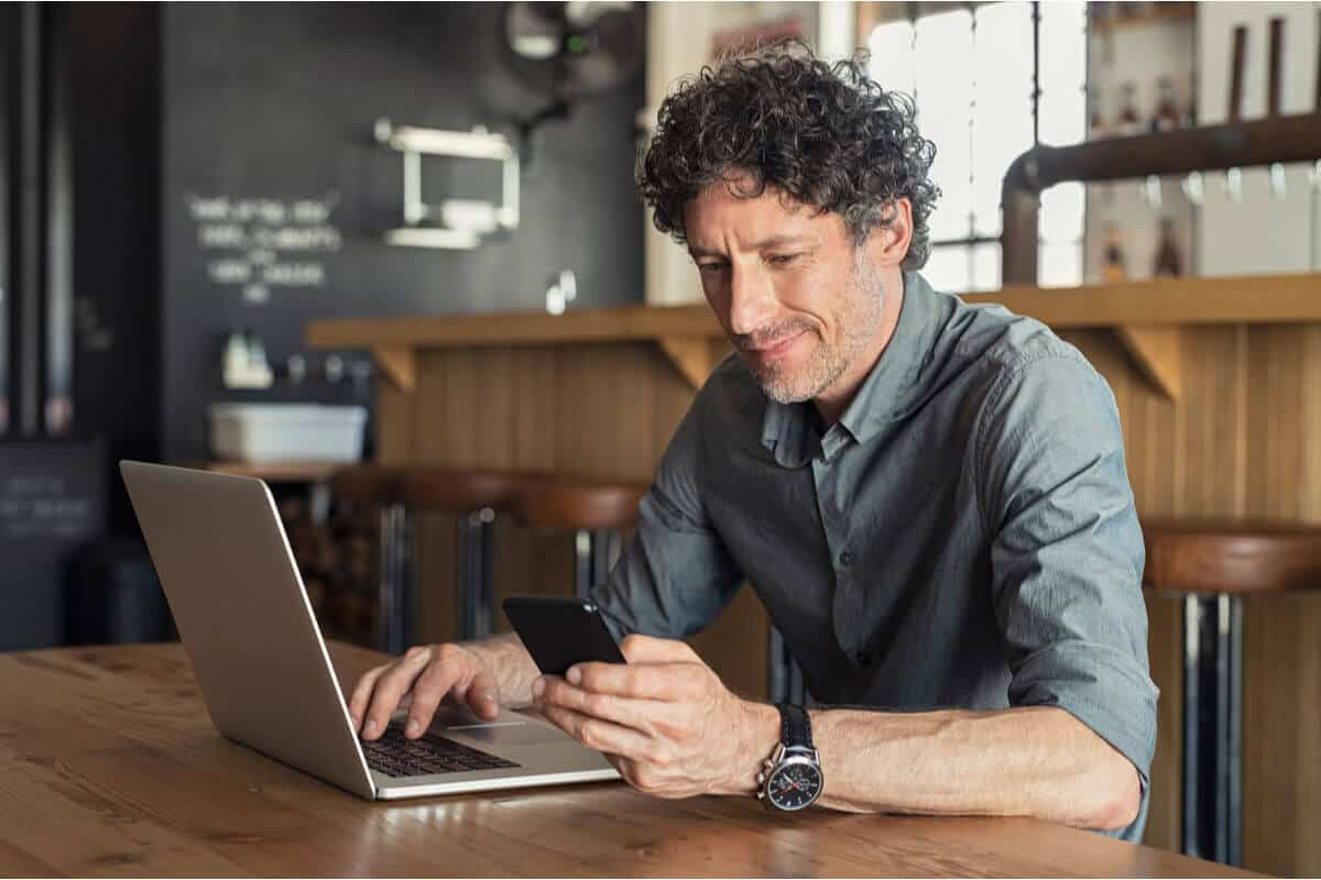 man sitting in coffee shop looking at phone and working on laptop