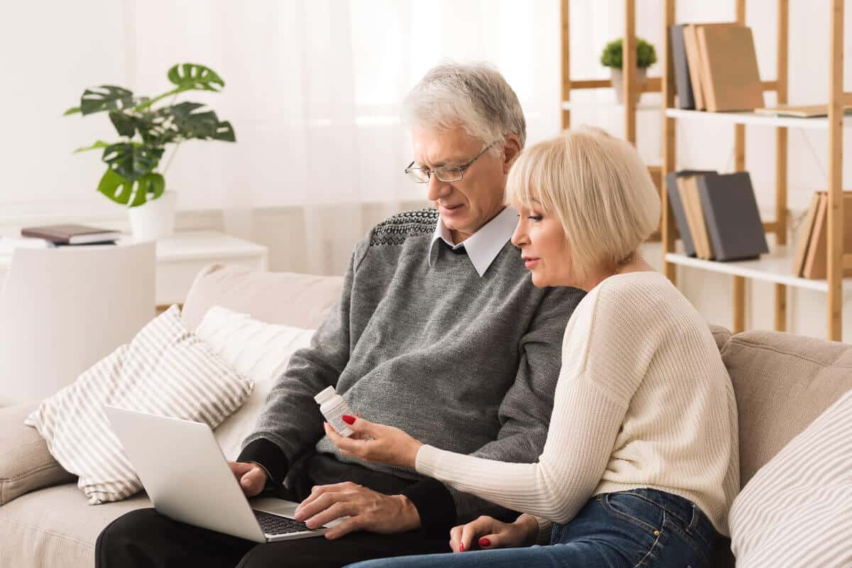 man and woman sitting on couch holding a supplement bottle and computer