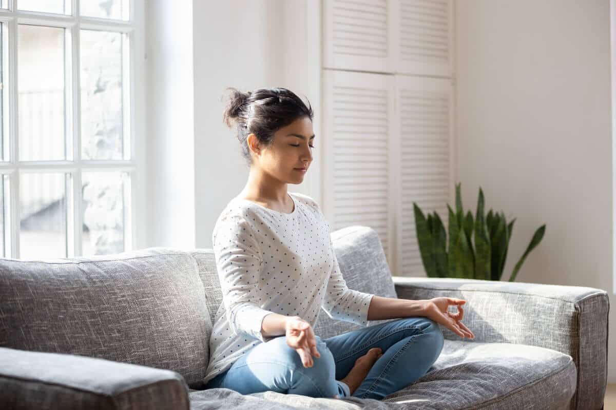 woman sitting on couch breathing and meditating
