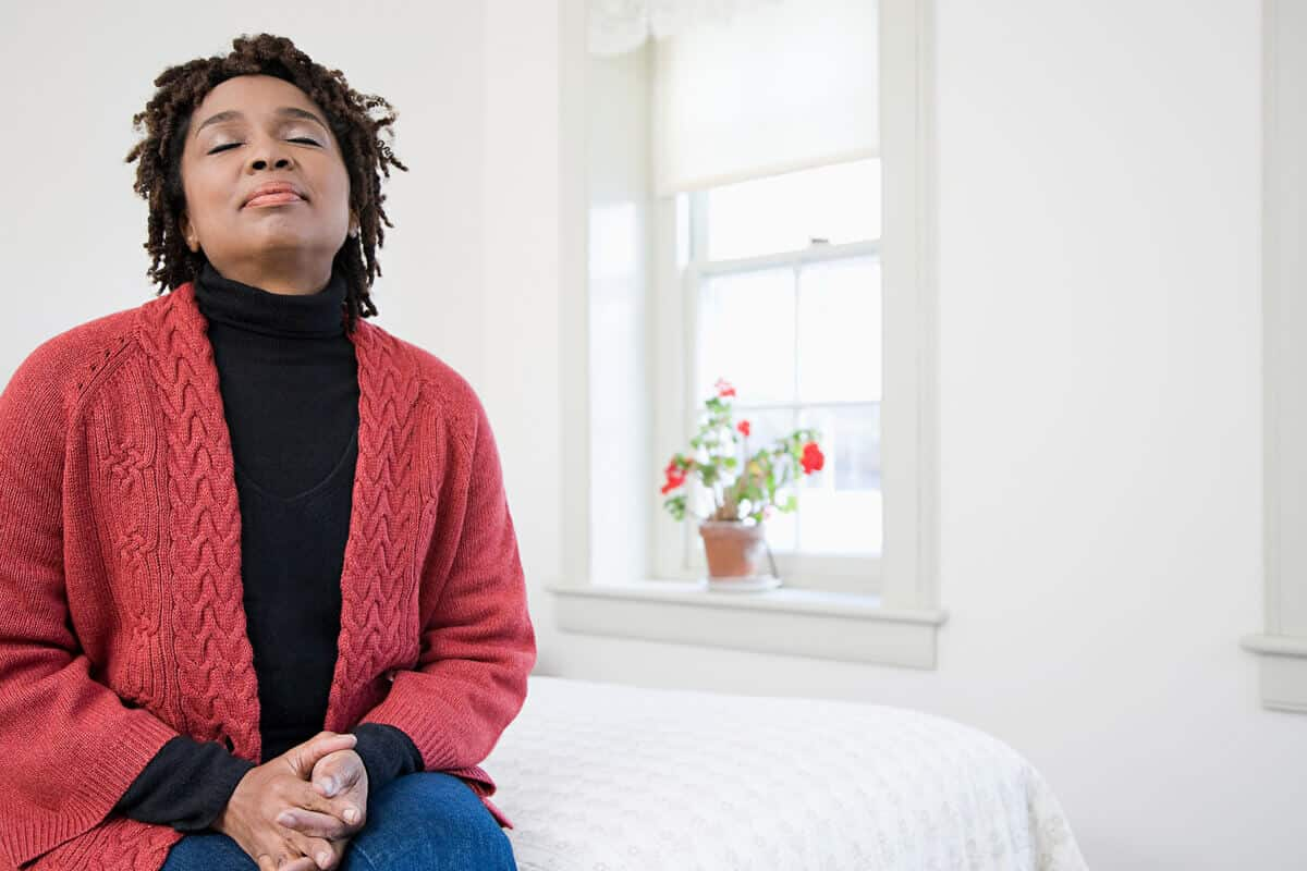 woman sitting on her bed breathing in