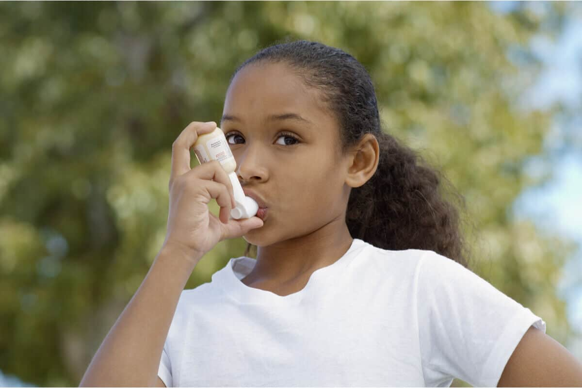 young girl using a puffer to breathe