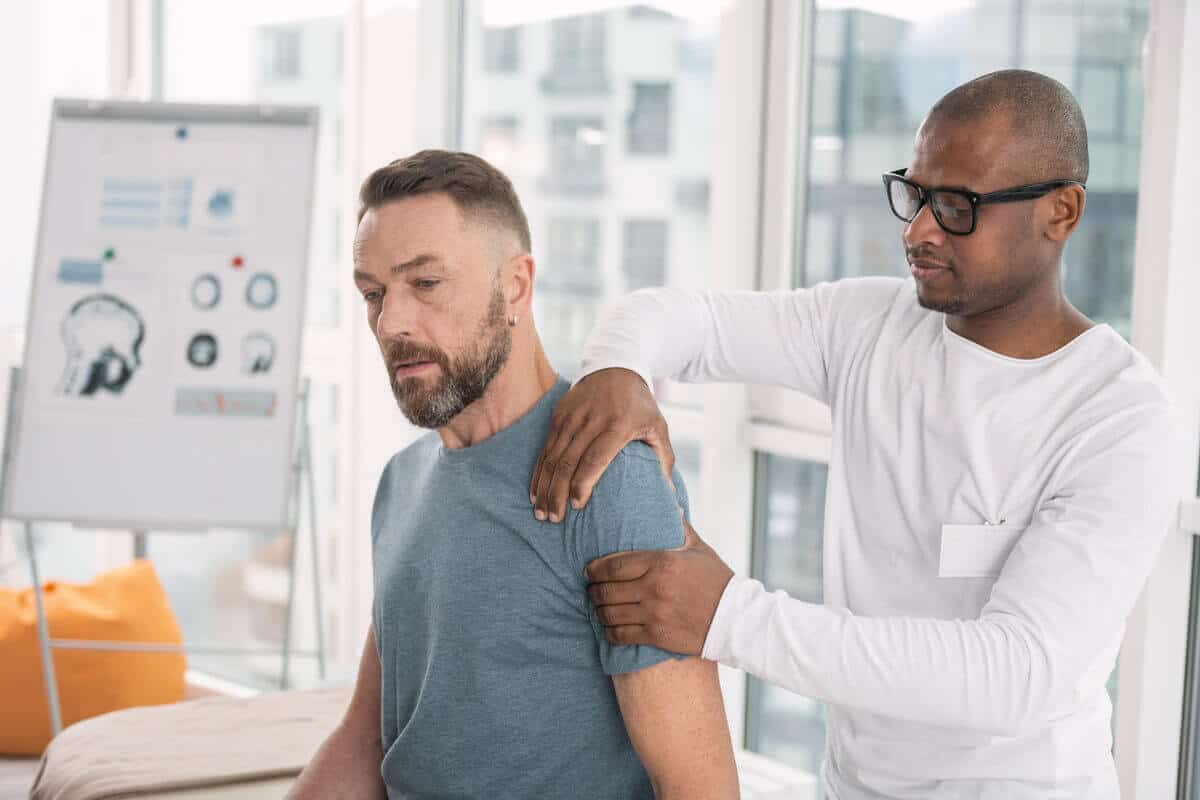 practitioner checking patients shoulder