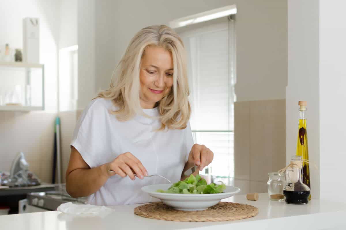 woman eating a salad in her kitchen
