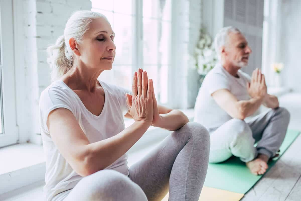 elder couple meditating together on yoga mats