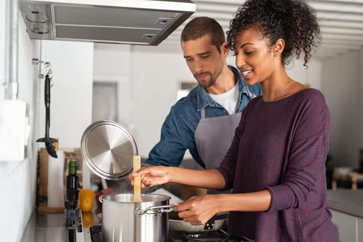 man and woman cooking in the kitchen, stirring a pot