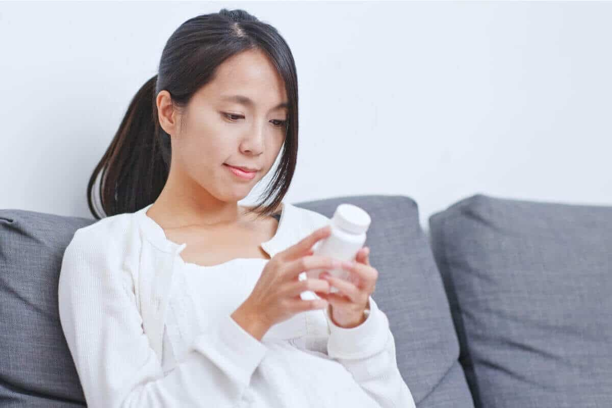 Woman looking at label on supplement bottle