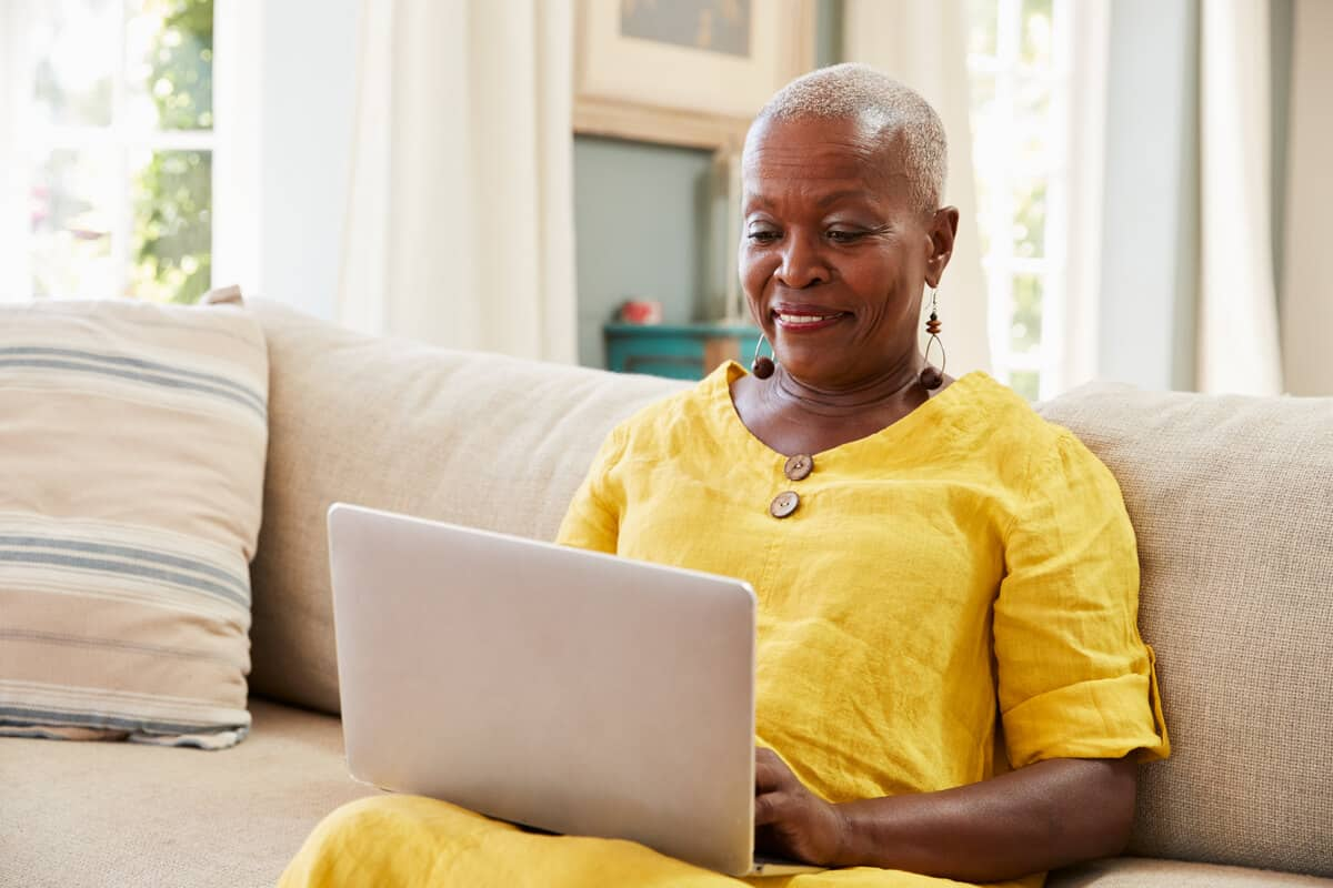 woman typing on her laptop sitting on her couch