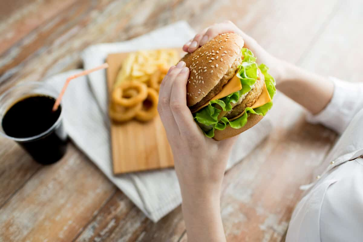 Image of person holding a cheeseburger