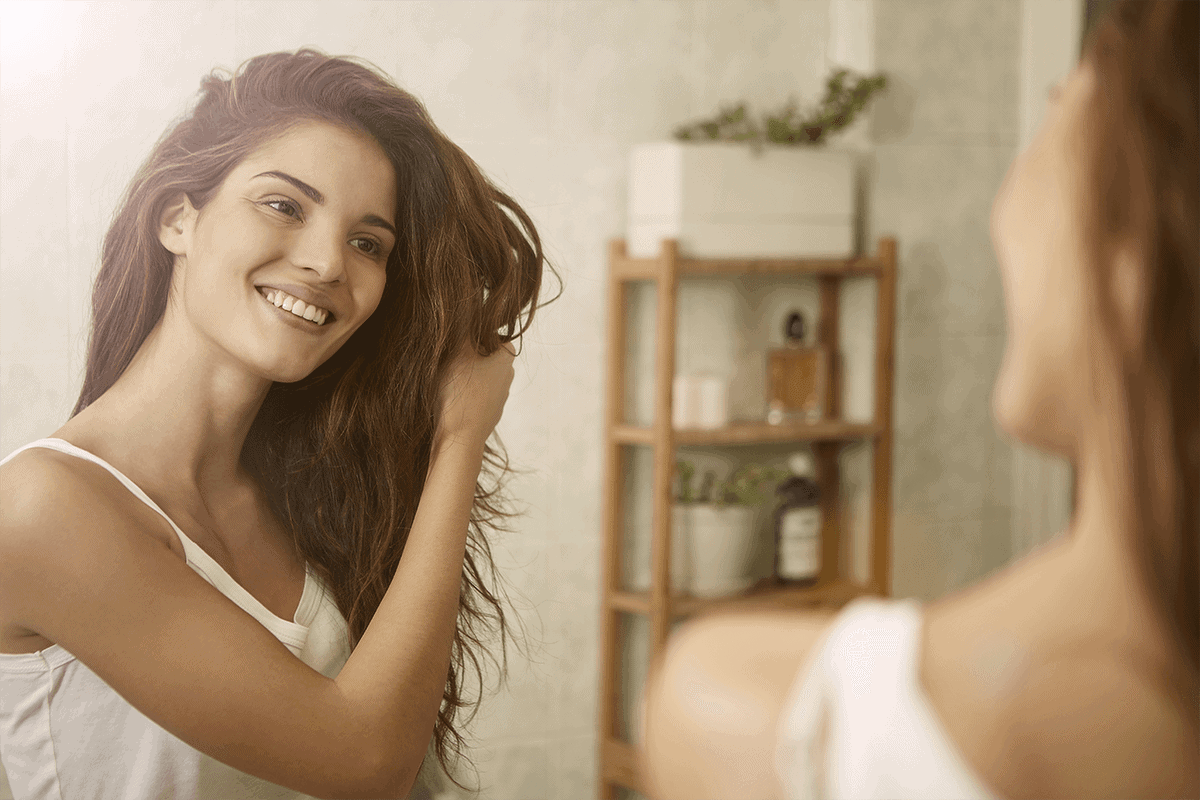 Image of woman holding hair and looking in the mirror