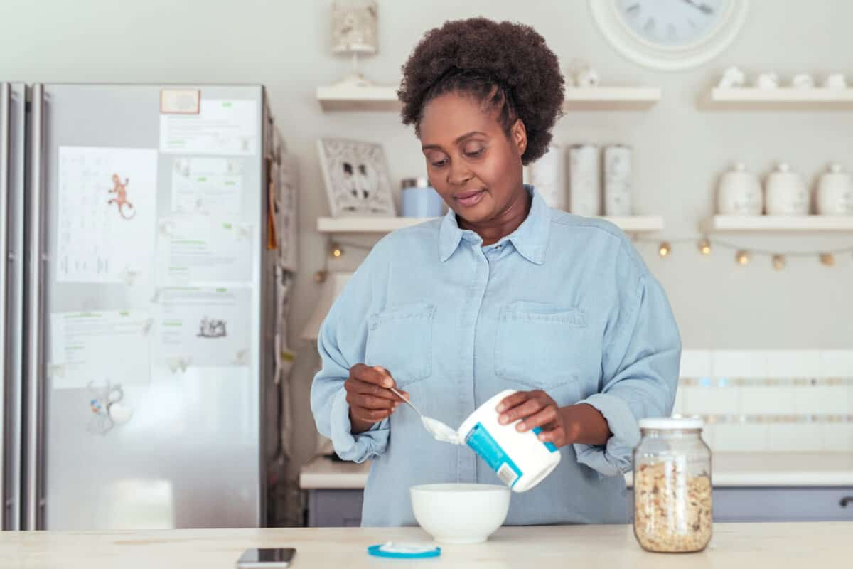 Woman scooping yogurt into a bowl