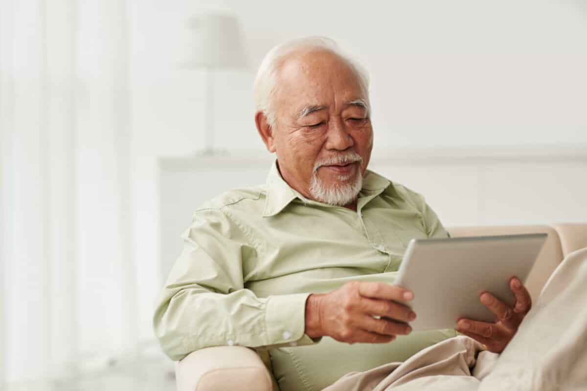 Elderly man reading on a tablet