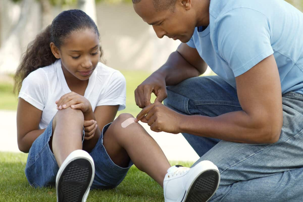 Man putting a bandage on a child