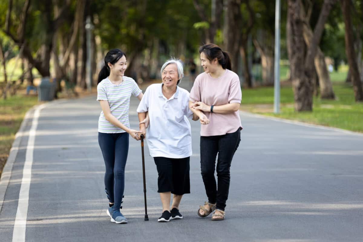 Two woman helping elderly woman down the street