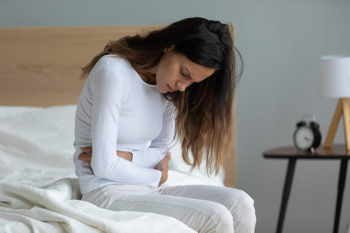 woman sitting on her bed holding her stomach in discomfort