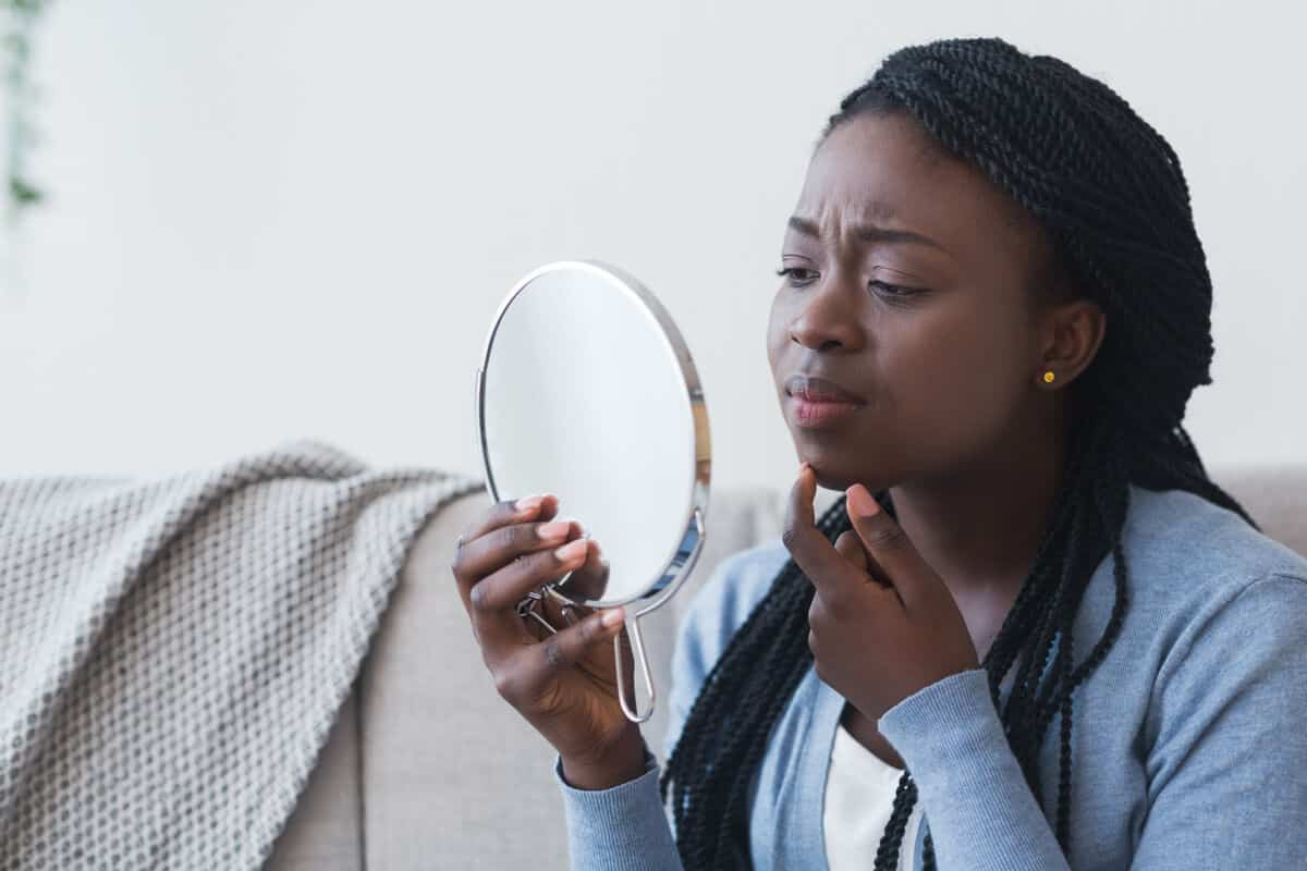 woman looking at her face in worry in a hand held mirror