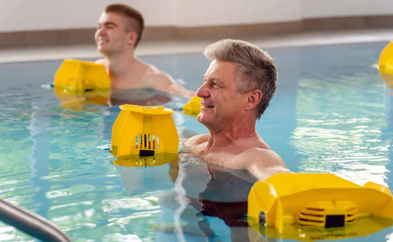 two men in pool doing water aerobic exercises
