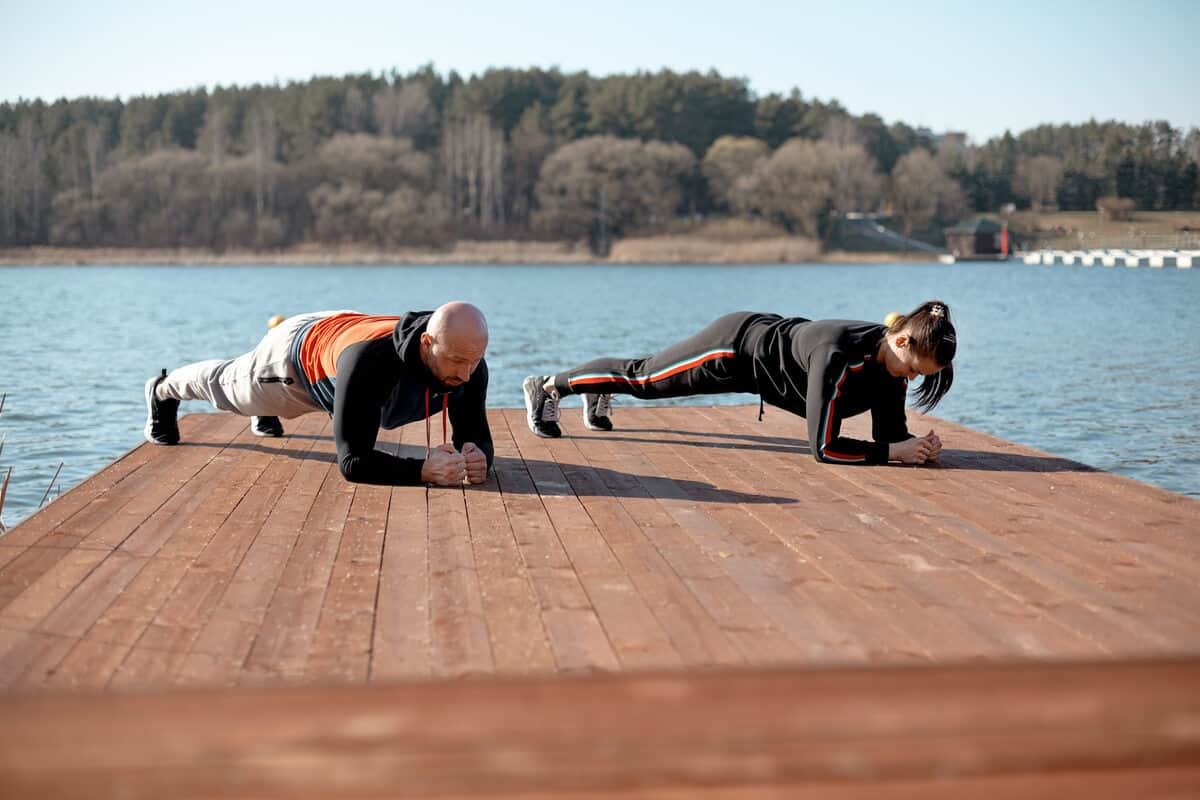 Two people planking on a dock