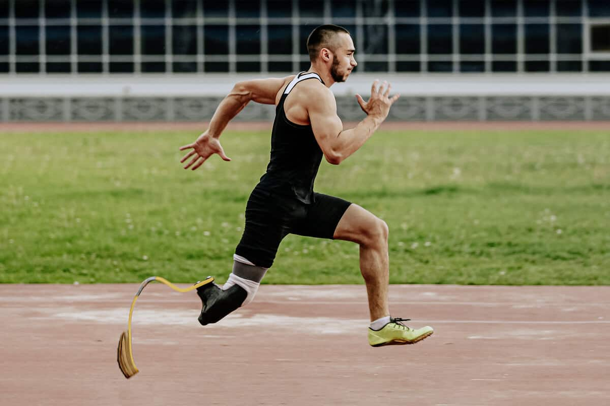 Man with an artificial leg running on a track