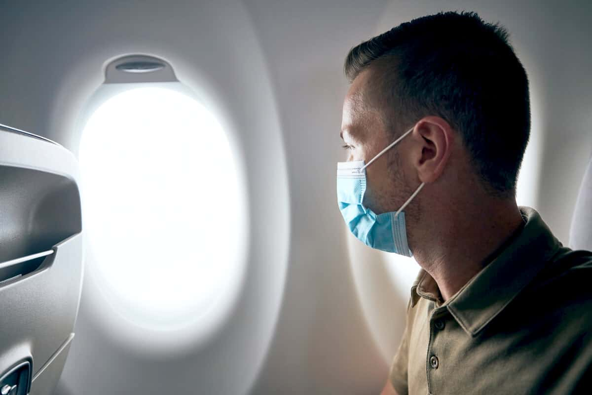 Man wearing a mask looking out the window of a plane