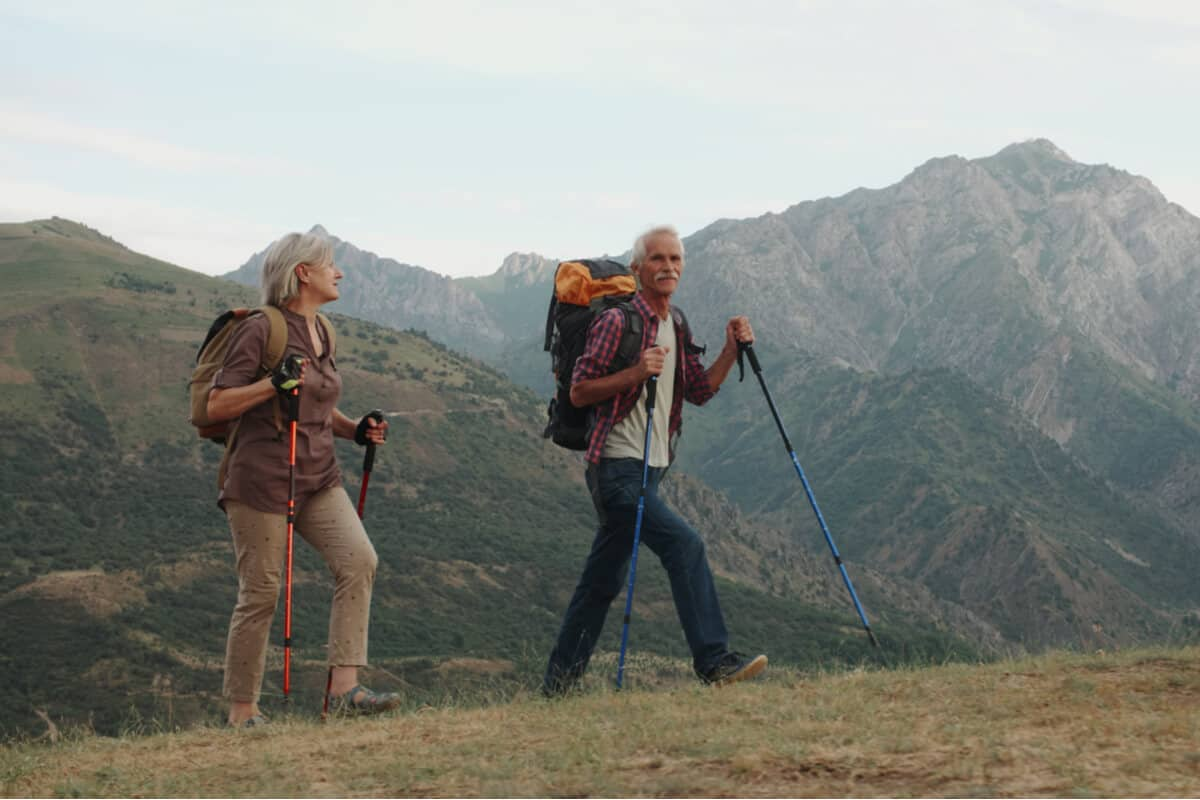 two people hiking with backpacks and hiking sticks