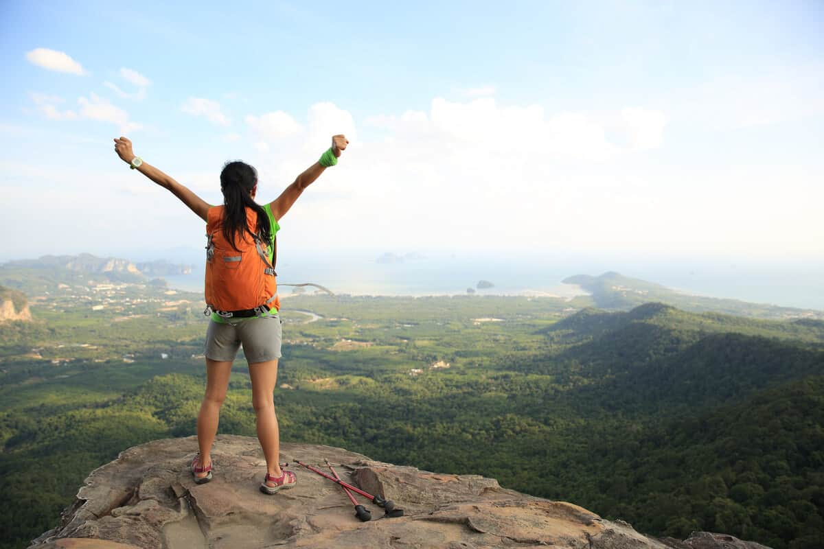 woman on top of a mountain with her arms up stretching