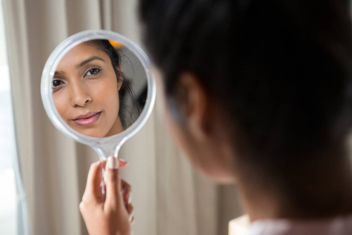 woman holding up a mirror and looking at herself in it