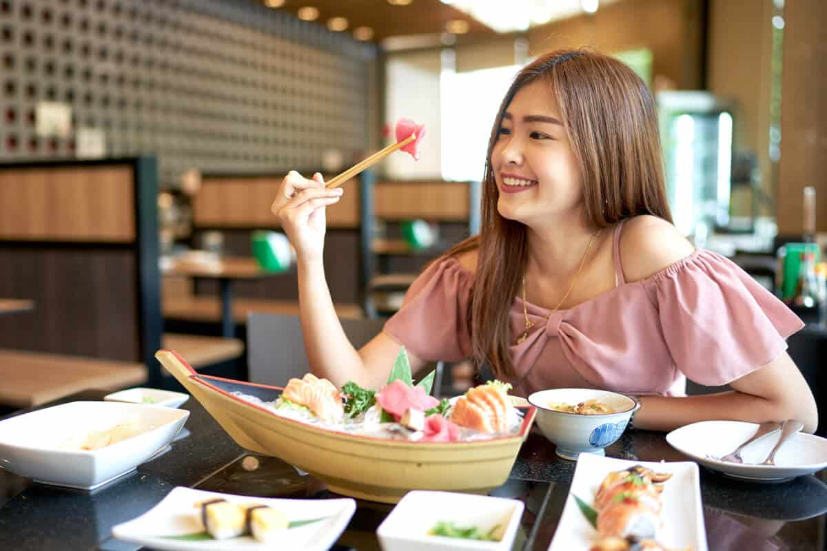 woman eating raw fish in a restaurant