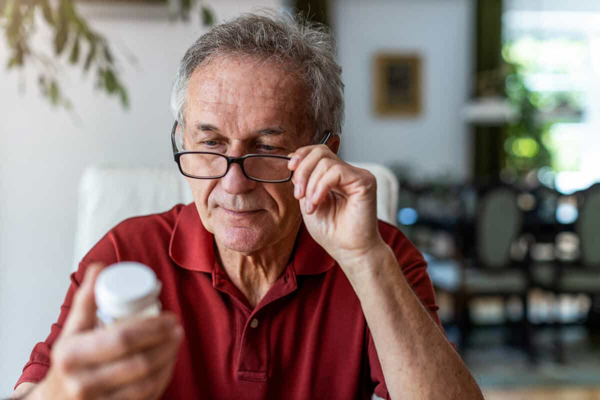 Man reading the label of a supplement bottle