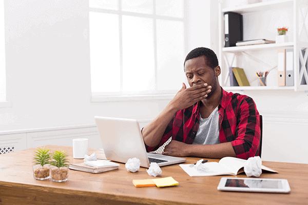 Man working on a laptop yawning