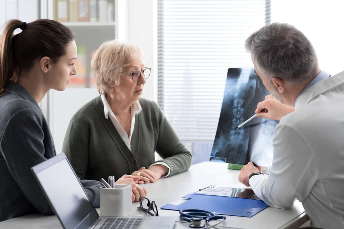 Practitioner showing patients an x-ray
