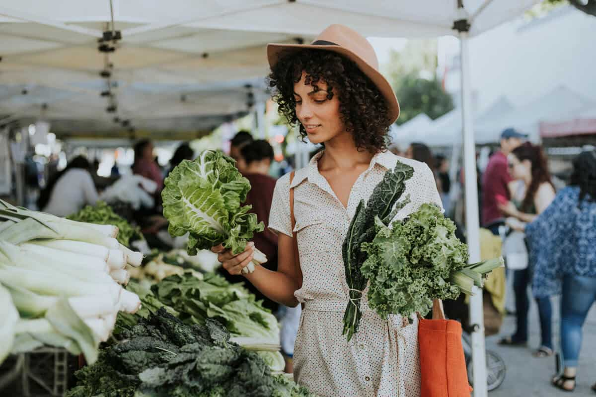 Woman picking vegetables at a farmers market