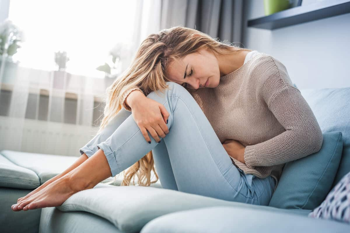 woman sitting on couch and holding her stomach in pain
