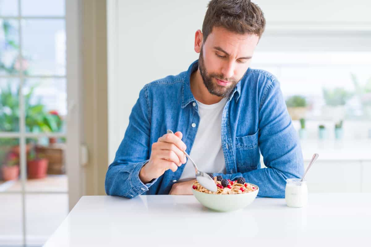 man sitting at kitchen table eating a bowl of yogurt with oats and berries