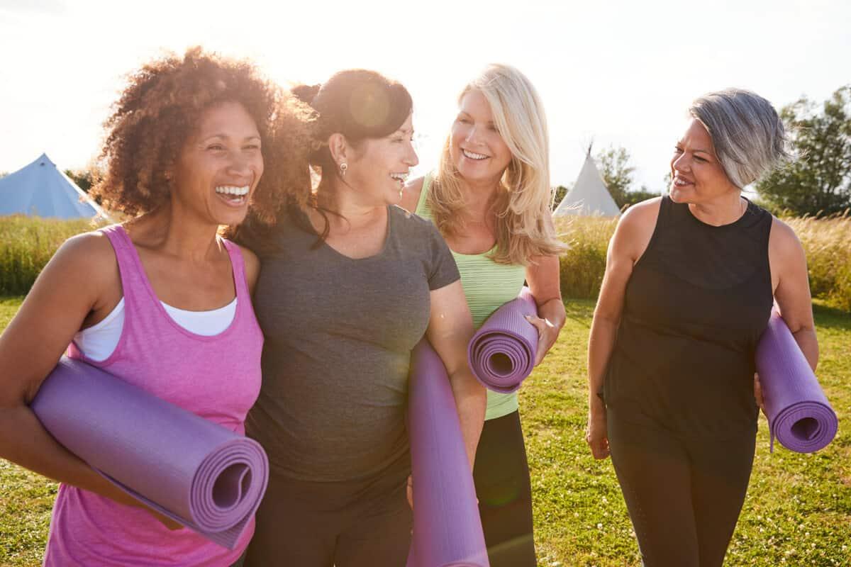 Woman carrying yoga mats laughing
