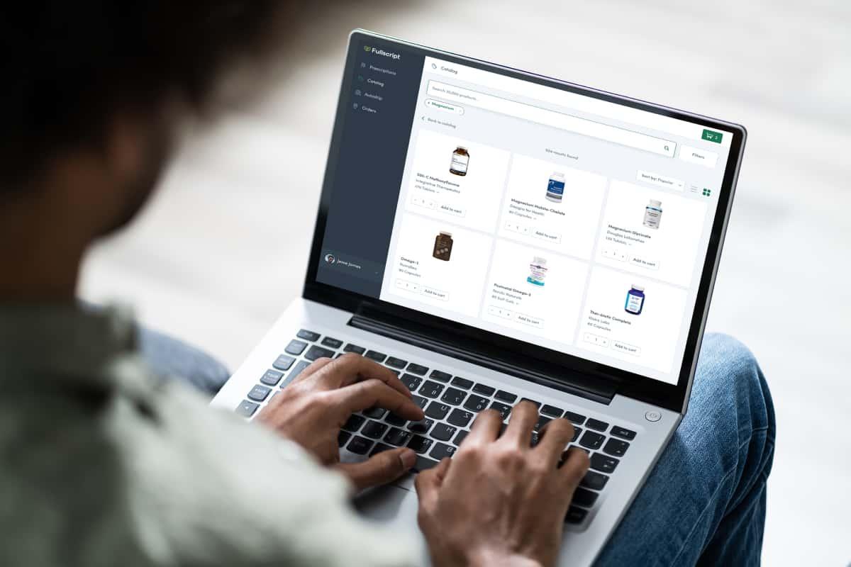 Person browsing the Fullscript catalog on laptop