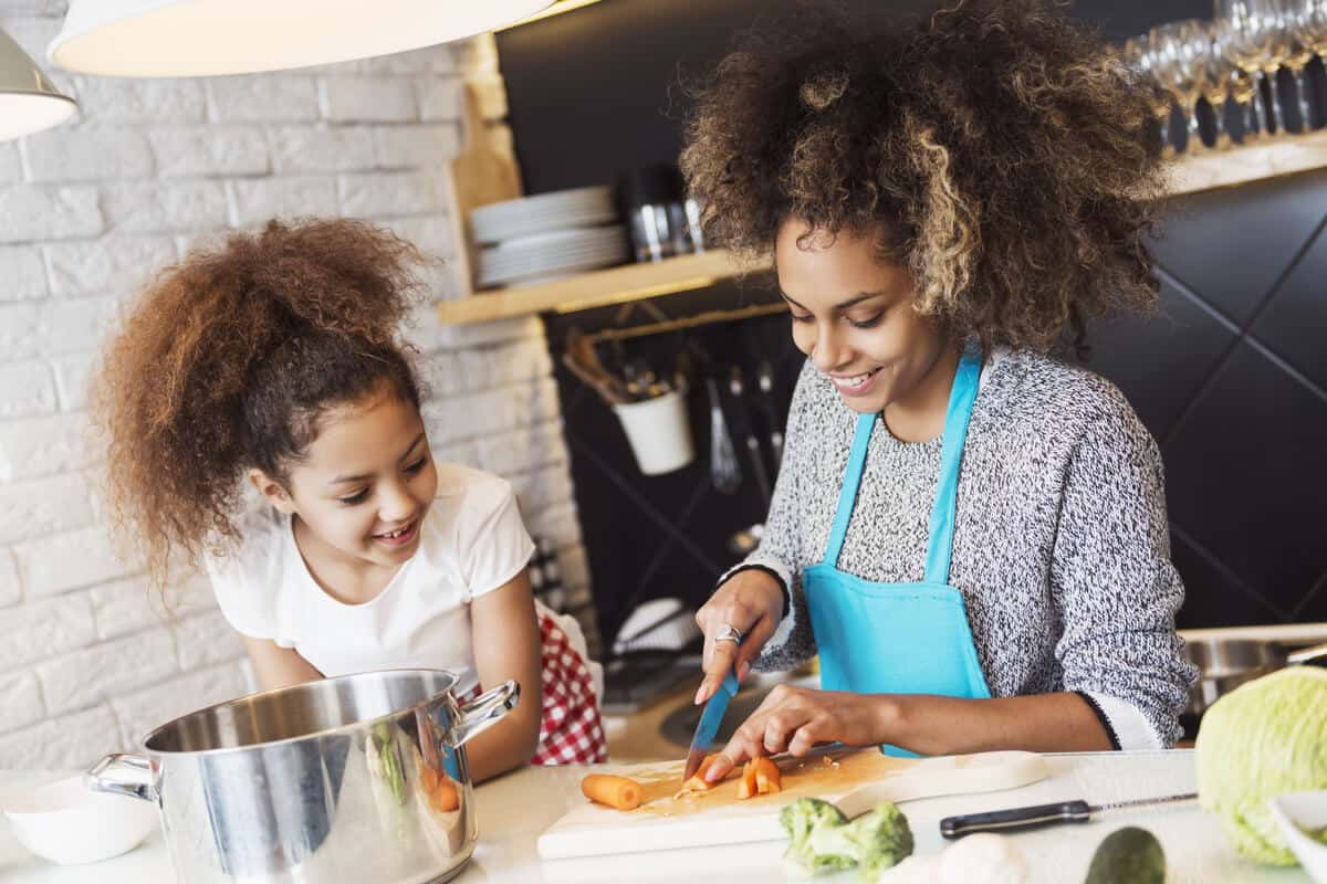 mom cutting up vegetables with young daughter