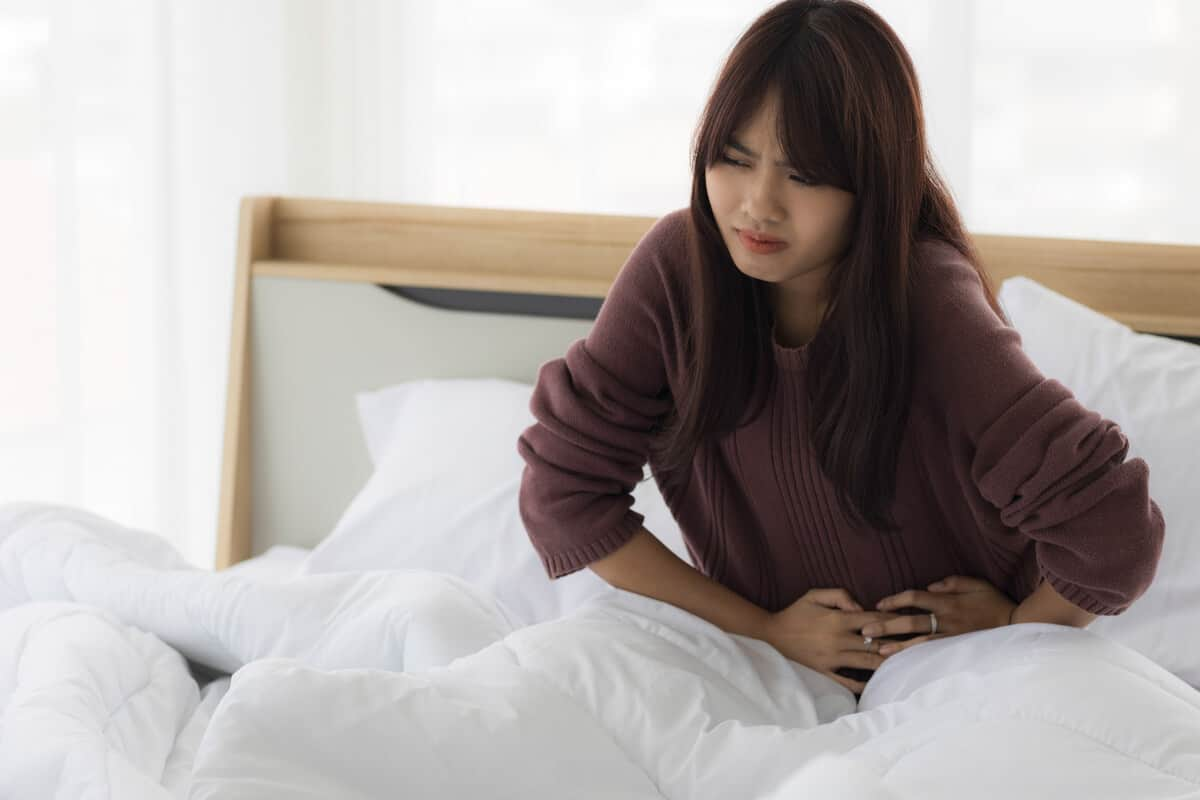 Woman laying in bed holding abdominal area