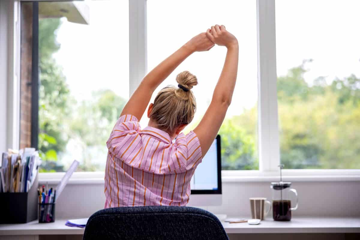 Woman siting at a desk stretching