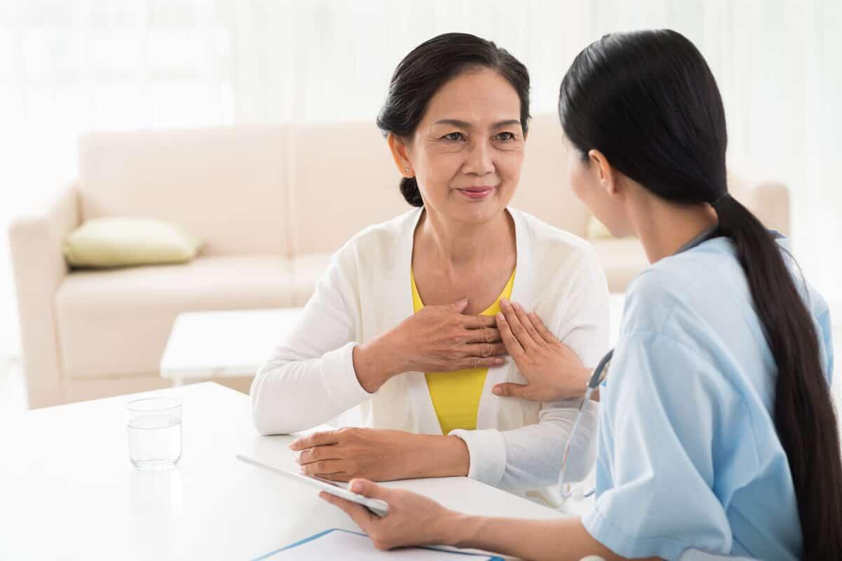healthcare worker feeling an elder woman's heart