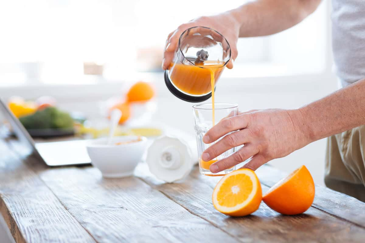 Man pouring a glass of orange juice